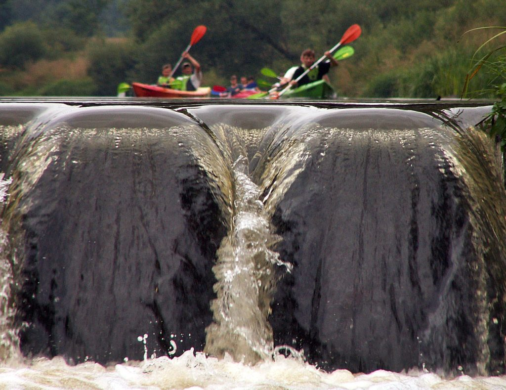 kayakers headed for a waterfall