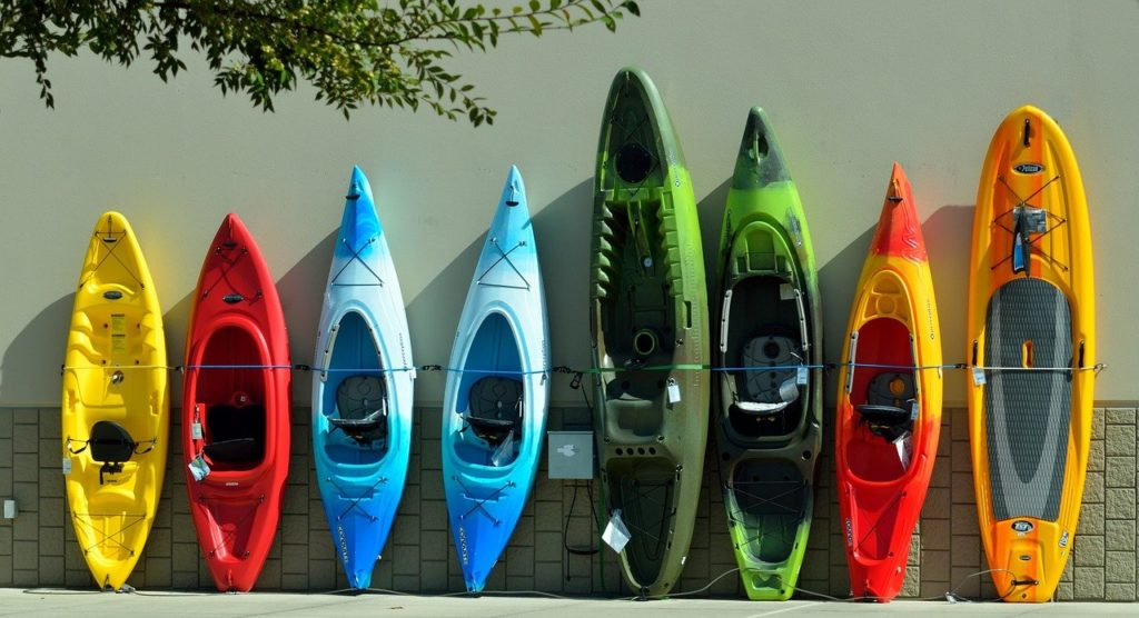 several colorful kayaks leaning up against a wall